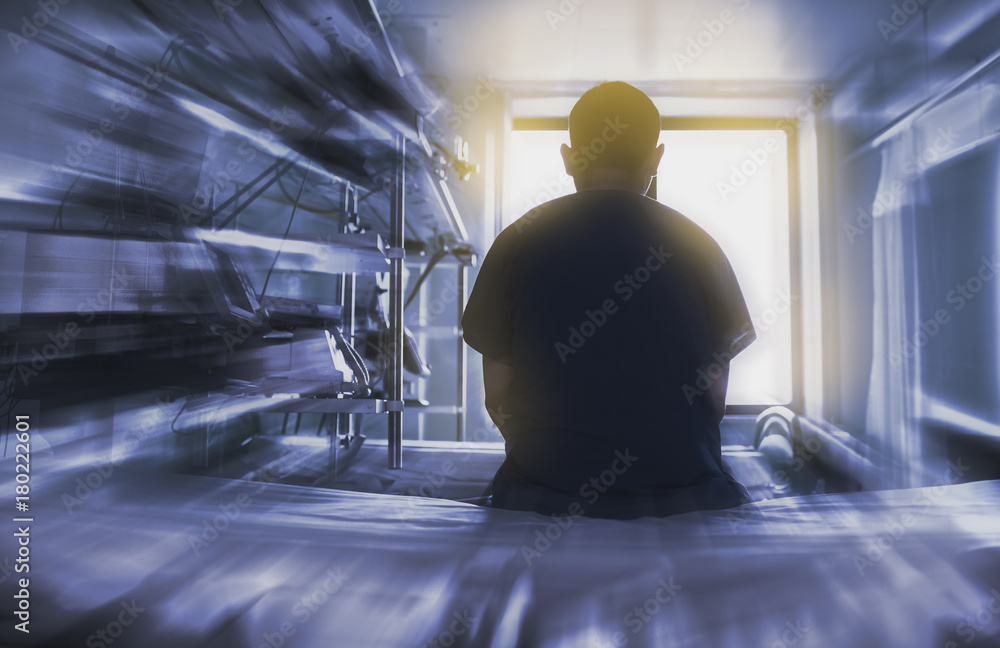 Fototapeta Man sitting on the hospital bed looking through the window, concept of dying patient