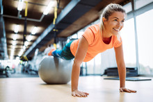 Young Attractive Woman Doing Push Ups Using Ball