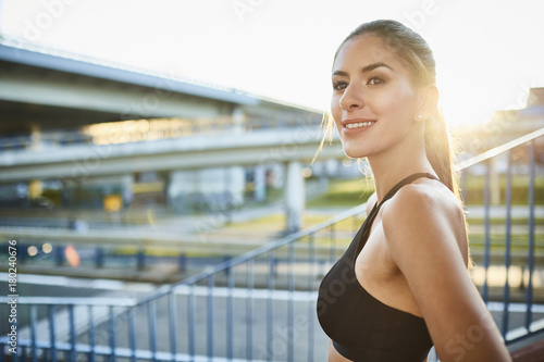 Portrait of smiling young woman during workout in the city