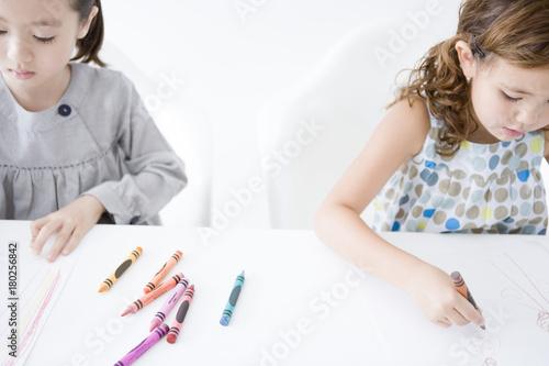 クレヨンで絵を描く女の子二人