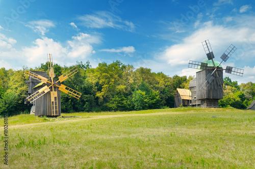 old wooden windmills in a field