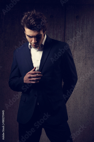 4f04c9f1 Handsome male model posing and looking down in fashion suit and white style  shirt on dark shadow background. Closeup portrait.