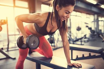 Fototapeta na wymiar Sportswoman in gym exercise muscles