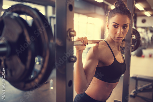 Fotografia, Obraz  Young female doing exercise with barbell