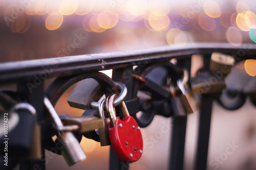 Fotografie, Obraz  Padlock pinned to the rail of the iron bridge with nice, fuzzy city lights in th