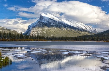 Distant Snowy Mountain Rundle Landscape reflected in calm water of Vermilion Lakes in Banff National Park after early Autumn Snowfall in Canadian Rocky Mountains