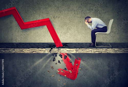 Fotografía  Depressed business man looking down at the falling red arrow going through a concrete floor