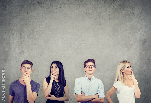 Fotografía  Portrait of two young men and two women thinking hard looking up standing near a concrete wall