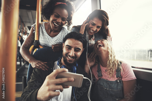 Photo  Smiling friends listening to music together on a bus