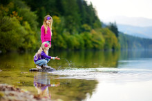 Adorable Sisters Playing By Hallstatter See Lake In Austria On Warm Summer Day. Cute Children Having Fun Splashing Water And Throwing Stones Into The Lake.