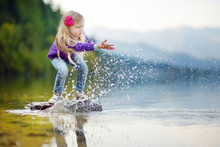 Adorable Girl Playing By Hallstatter See Lake In Austria On Warm Summer Day. Cute Child Having Fun Splashing Water And Throwing Stones Into The Lake.