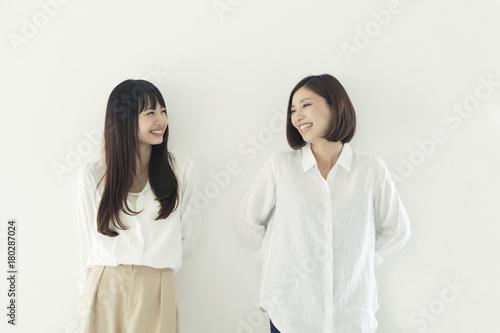 仲良く並んで微笑む20代女性2人