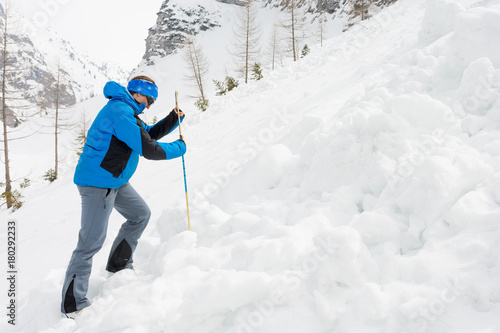 Photo Female rescuer searching for avalanche victim.
