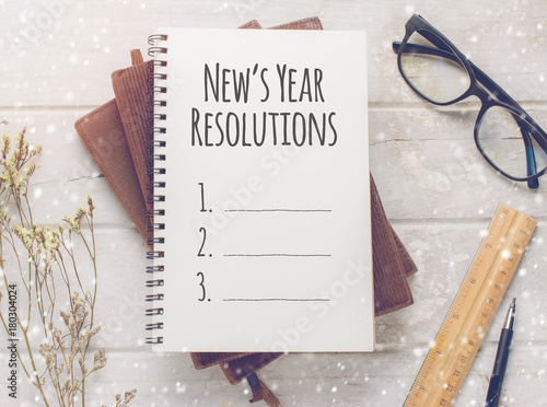 Fotografie, Obraz  Notebook with New's Year Resolutions massage, glasses and working ornament on white wooden table background