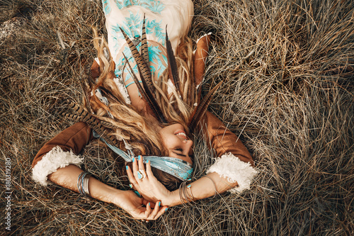 beautiful young boho girl in jacket lying down on grass Canvas Print