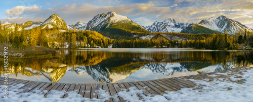 Staande foto Bleke violet frosted bridge over the mountain lake Strbske Pleso in Slovakia, snowy mountains reflecting in the water