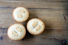Overhead Shot Of Three Mince Pies On A Wooden Table, A Traditional Christmas Dessert. Copy Space For Text