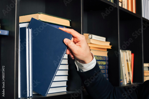 Obraz na plátně  a masculine hand takes a book from a bookshelf