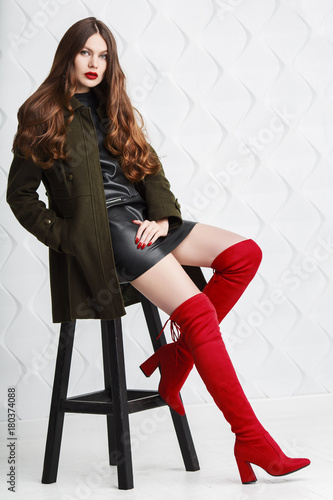 Fototapeta Full body studio portrait of beautiful fashionable woman posing on white geometric background. Model wearing stylish leather dress, green coat, red high boots with heels. Female fashion concept obraz