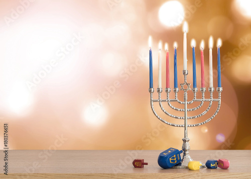 Hanukkah Jewish holiday background with menorah (Judaism candelabra)  burning candles and traditional Dreidrel game toy on wood table and on autumn bokeh sun flare