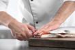 Chef cutting fresh salmon in kitchen