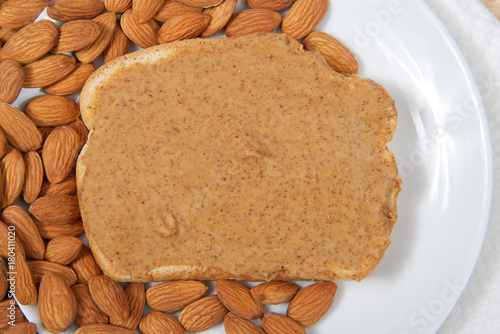 Valokuva  Almond butter spread on bread on a white plate surrounded by whole raw almonds