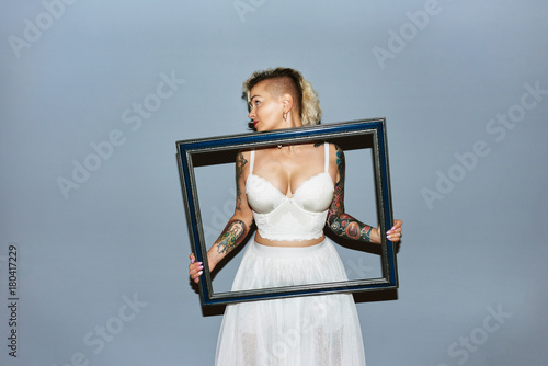 Photo  Freaky blond girl with picture frame bringing attention to breasts