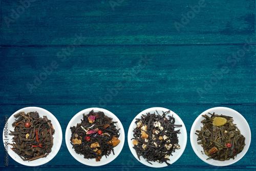 Photo  Tea blendss on strands in presenters on blue wooden background