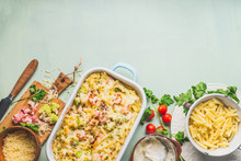 Pasta Casserole With Romanesco Cabbage And Ham In Creamy Sauce, On Kitchen Table Background With Ingredients, Top View, Border.  Italian Cuisine