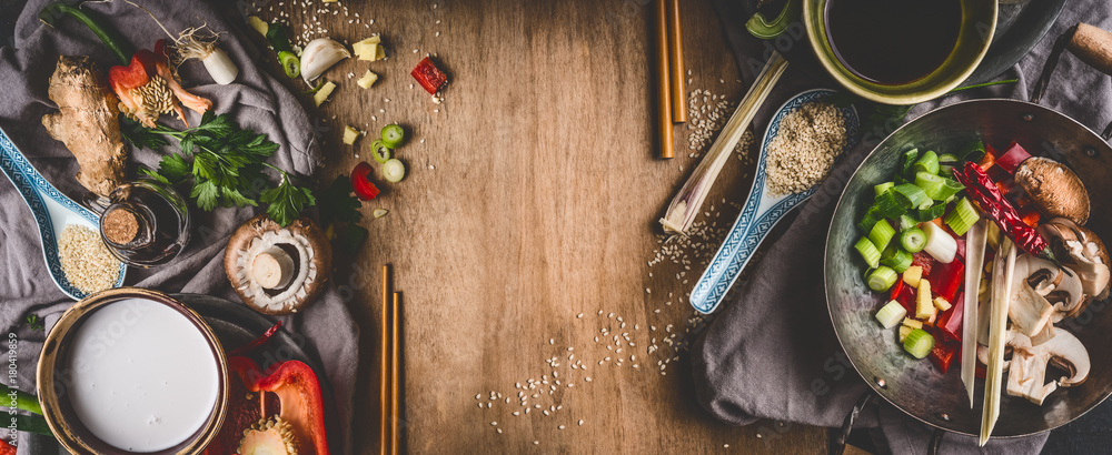 Fototapety, obrazy: Vegetarian Asian cuisine ingredients for stir fry with chopped vegetables, coco milk, spices,chopsticks and wok pot on rustic wooden background, top view, banner. Chinese or Thai food cooking