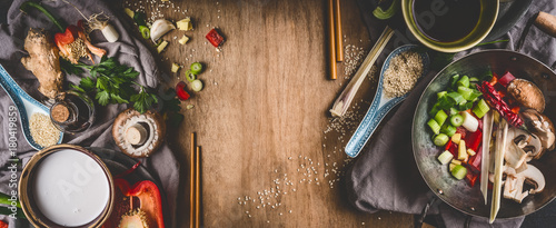 Fototapeta Vegetarian Asian cuisine ingredients for stir fry with chopped vegetables, coco milk, spices,chopsticks and wok pot on rustic wooden background, top view, banner. Chinese or Thai food cooking obraz