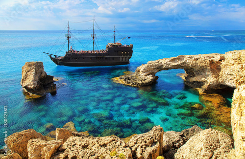 The bridge of love or love bridge. Pirate ship sailing near famous Bridge of Love near Ayia Napa, Cyprus.