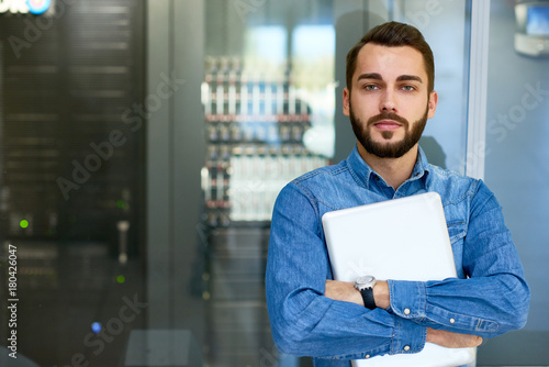 Leinwand Poster Portrait of beraded systems administrator posing holding laptop and looking at c