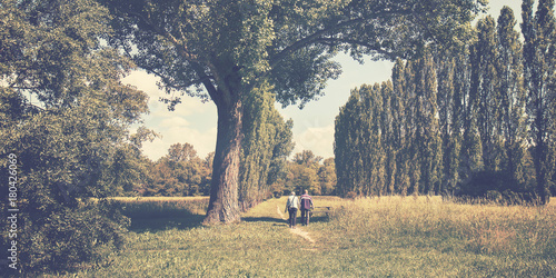 Plakat Dwie osoby chodzą po szlaku, poziome zdjęcie starych znajomych spędza czas w naturze