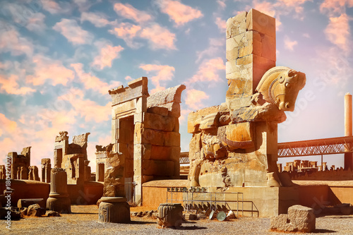 Fotografie, Obraz  Stone sculpture of a horse in Persepolis against a blue and pink sky with clouds
