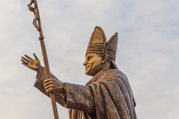 Ancient brass sculpture of Pope, the bishop of Rome with golden sunlight glare on the statue.