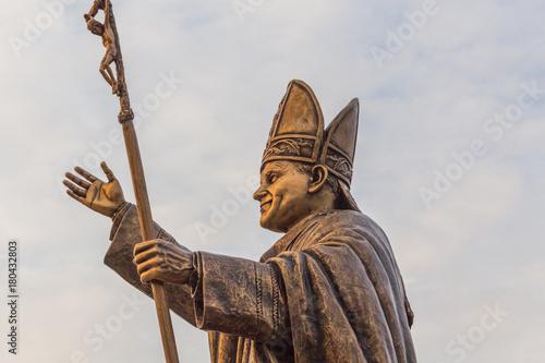 Antyczna mosiężna rzeźba papieża, biskupa Rzymu ze złotym blaskiem słońca na posągu.