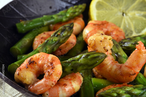 fried prawns or shrimps with  green asparagus peaks and a lemon slice in a black iron pan, close up