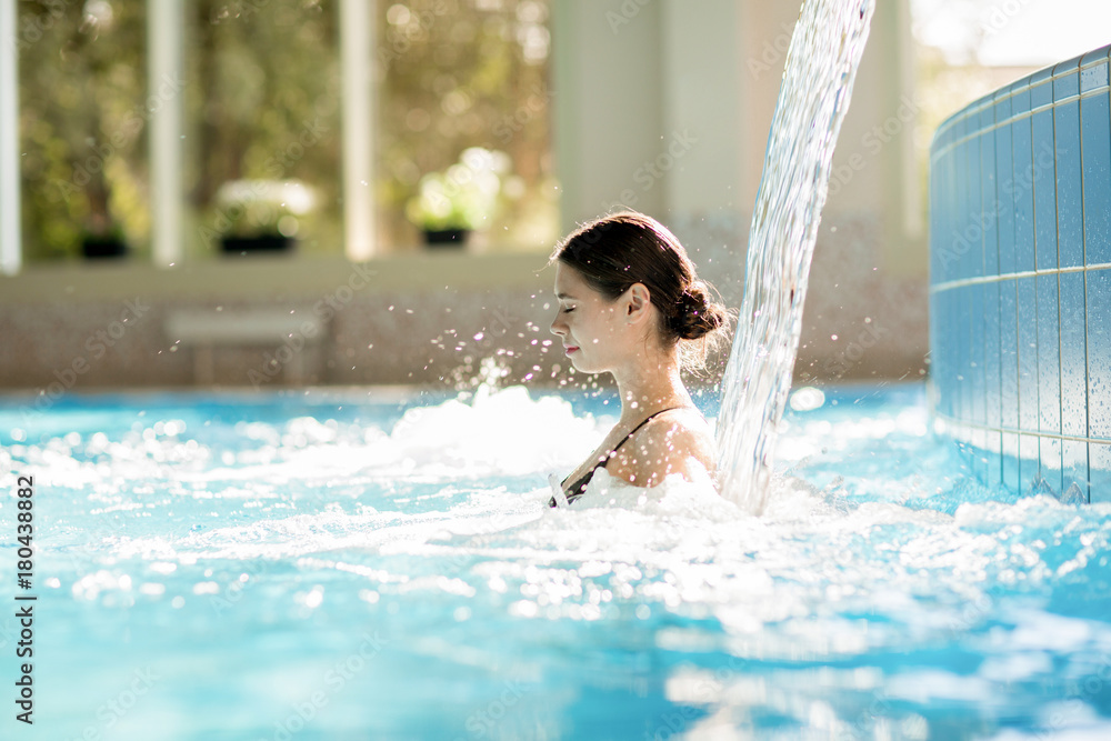 Fototapeta Serene girl enjoying stream of waterfall and its gentle splashes in swimming-pool at spa resort
