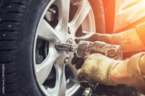 Car mechanic worker doing tire or wheel replacement with pneumatic wrench in gar Wallpaper Mural