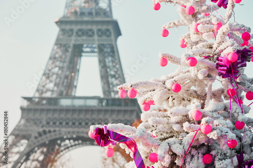 Christmas tree covered with snow near the Eiffel tower in Paris Canvas Print