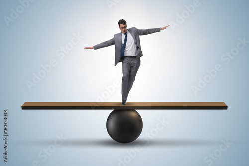 Fotomural Businessman trying to balance on ball and seesaw