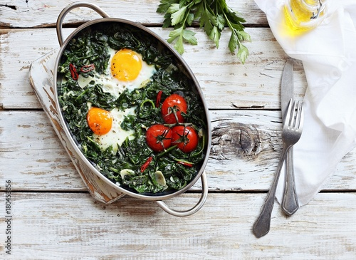 Deurstickers Gebakken Eieren Eggs baked with spinach and tomatoes in serving pan overhead rustic wooden table. Overhead view.