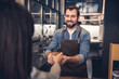 Portrait of smiling bearded worker holding out hand with mug of beverage to woman in modern cafe. Order concept