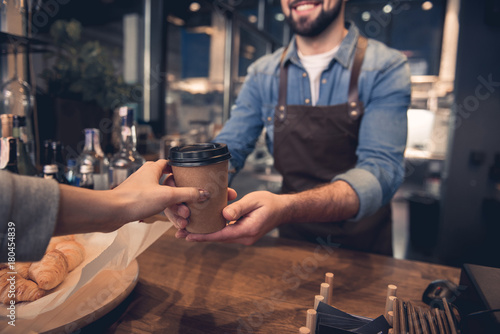 Photo Close up female hand taking cup of hot coffee from barista in confectionary shop