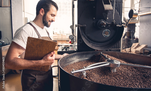 Photo  Side view cheerful bearded worker checking grains situating in special equipment