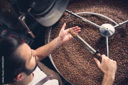 Photo  Top view serious bearded worker near coffee roaster controlling level of grain roasting