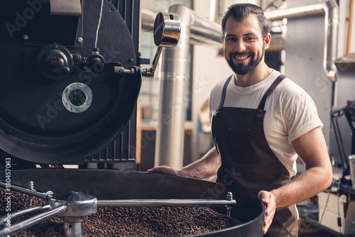Photo  Portrait of cheerful unshaven worker checking burning seeds in grain chiller