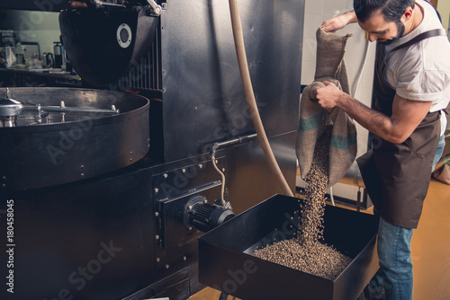 Poster Café en grains Side view outgoing bearded male worker pouring coffee beans in case. Prepare concept