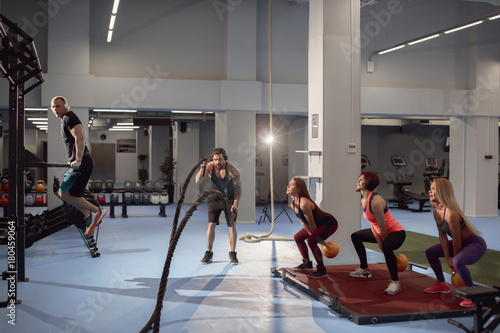 Keuken foto achterwand Ontspanning Group of fit and muscular people practicing with barbell on gym